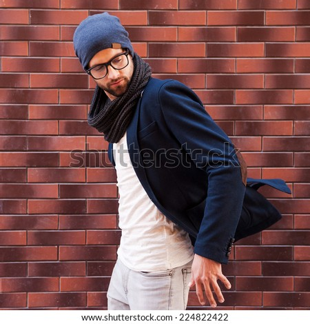 Confident in his trendy look. Handsome young man in eyeglasses adjusting his jacket and looking away while standing against brick wall - stock photo