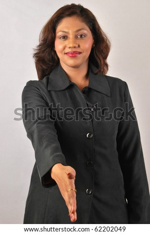confident Indian business woman shaking hands - stock photo