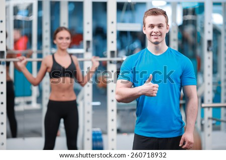 Confident instructor. Handsome sports instructor showing his thumb up while young beautiful woman in sports clothing posing with a barbell  - stock photo
