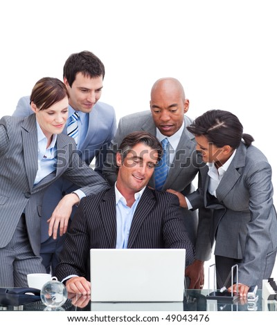 Confident international business team looking at a laptop in the office