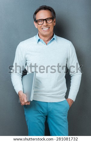 Confident IT professional. Happy mature man holding laptop and hand in pocket while standing against grey background - stock photo