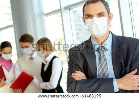 Confident leader in protective mask looking at camera in working environment - stock photo