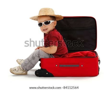 Confident little boy wearing sunglasses and straw hat, sitting in open suitcase - stock photo