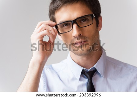 Confident look. Portrait of handsome young man in shirt and tie adjusting his eyeglasses and looking at camera while standing against grey background - stock photo