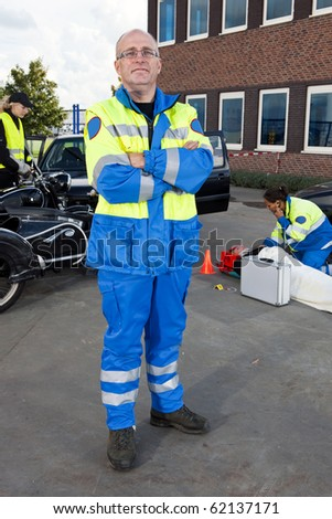 Confident looking paramedic posing for the camera in front of a car crash - stock photo