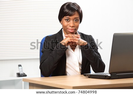 Confident looking young black business woman in office sitting to her desk resting her chin on folded hands. - stock photo
