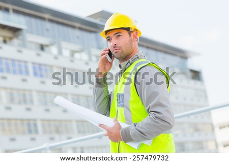 Confident male architect with blueprints using mobile phone against building - stock photo