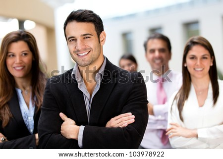 Confident male business leader with his team - stock photo
