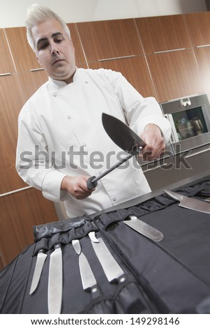 Confident male chef sharpening knives in commercial kitchen - stock photo
