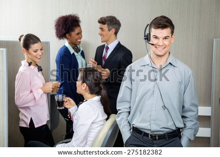 Confident male customer service representative wearing headphones while manager discussing with team in background at call center - stock photo