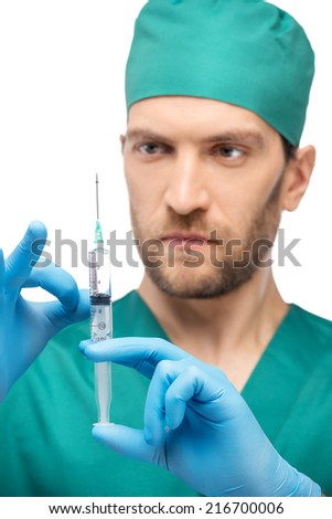 Confident male doctor with syringe - stock photo