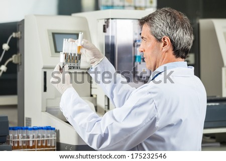 Confident male researcher analyzing urine samples in lab