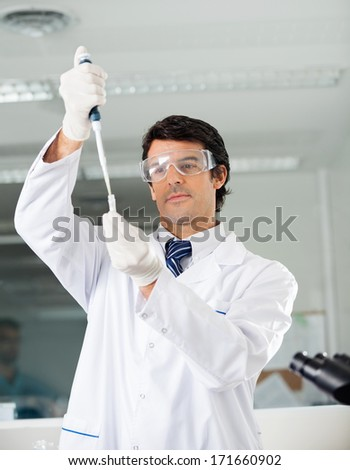 Confident male scientist filling solution into test tube in medical lab