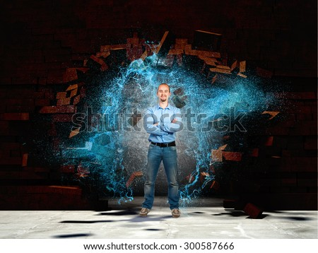 confident man broken brick wall and water spalsh explosion - stock photo