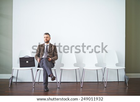 Confident man in formalwear waiting for his turn for interview - stock photo