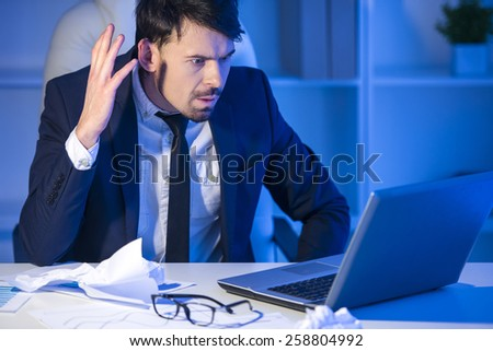 Confident man is working on laptop in office - stock photo
