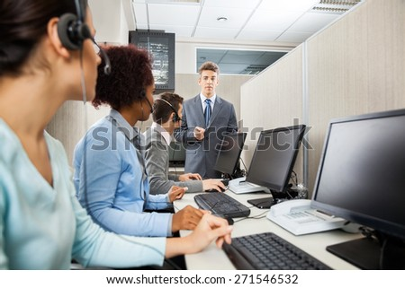 Confident manager in discussion with customer service representatives in office - stock photo