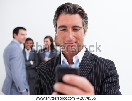 Confident manager sending a text with a mobile phone with his team in the background - stock photo
