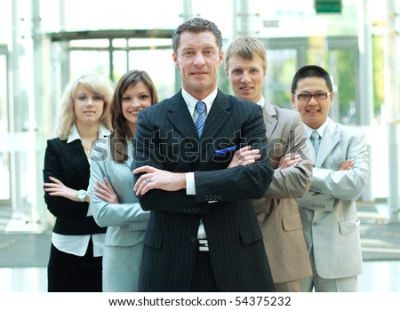 Confident mature business man with colleagues at the background - stock photo