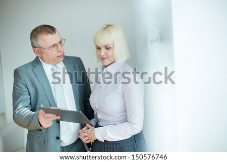 Confident mature businessman looking at his colleague while commenting document - stock photo
