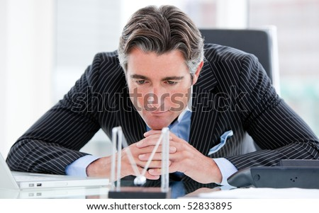Confident mature businessman looking at kinetic balls sitting at his desk - stock photo