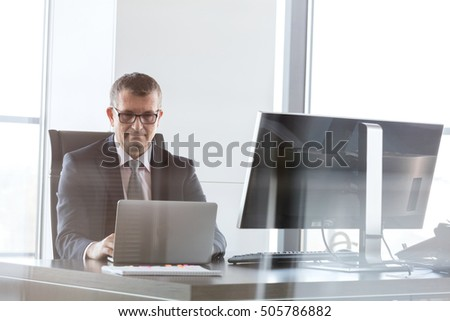 Confident mature businessman using laptop at desk in office