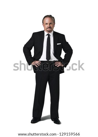 Confident mature businessman with hands in pocket against white background
