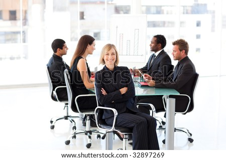 Confident mature businesswoman sitting with folded arms in a meeting