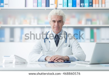 Confident mature doctor posing in his office and smiling at camera, healthcare concept