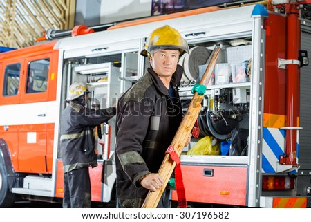 Confident mature fireman holding wooden stretcher against truck at fire station - stock photo