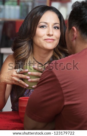 Confident mature Latino woman with man at table - stock photo