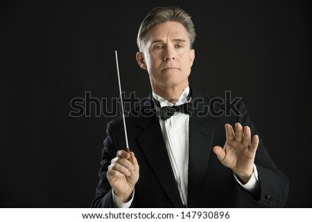 Confident mature male orchestra conductor directing with his baton against black background - stock photo