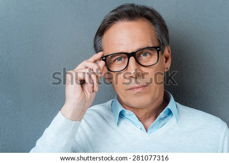 Confident mature man. Confident mature man adjusting his eyewear and looking at camera while standing against grey background - stock photo