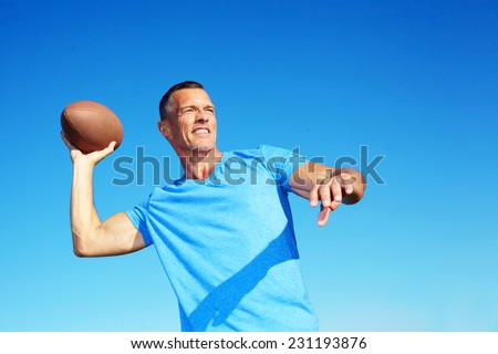 Confident mature man throwing American football against clear blue sky - stock photo