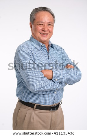 Confident mature Vietnamese man standing with his arms crossed - stock photo