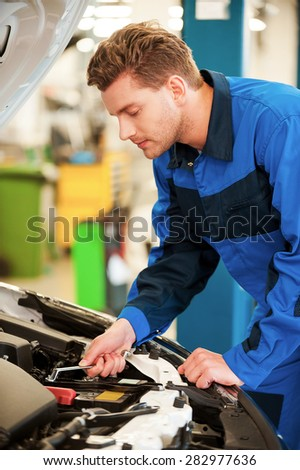 Confident mechanic at work. Concentrated young man in uniform repairing car while standing in workshop