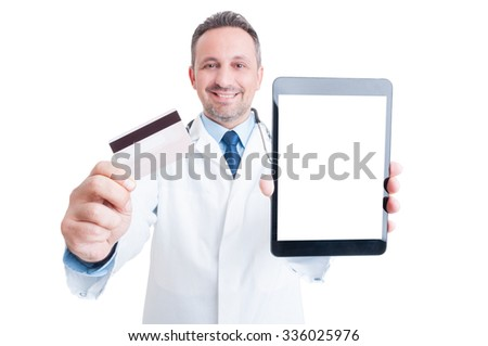 Confident medic or doctor showing credit card and blank screen tablet with copy space and advertising area - stock photo