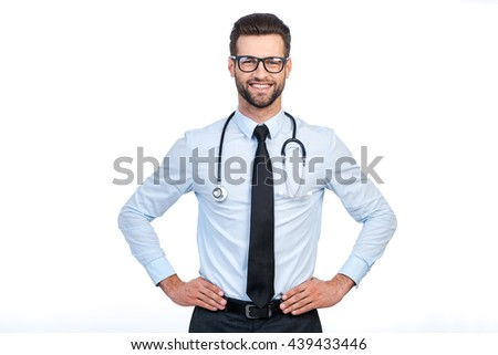 Confident medical expert. Confident young handsome man in shirt and tie carrying stethoscope on shoulders and looking at camera with smile while standing against white background  - stock photo
