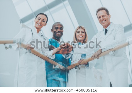 Confident medical experts. Low angle view of four happy medical doctors standing close to each other and holding their hands together while leaning at the handrail - stock photo