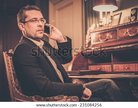 Confident middle-aged man with mobile phone in luxury interior  - stock photo