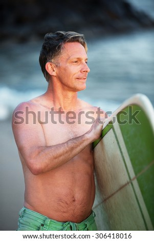 Confident middle aged surfer with surfboard looking over