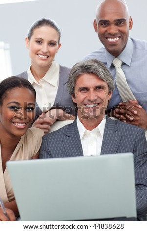 Confident Multi-ethnic business team working at a laptop in a meeting