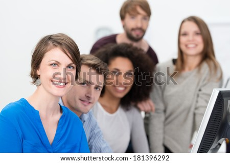 Confident multiethnic young business team lead by a smiling attractive young women working together in the office at a desktop computer - stock photo