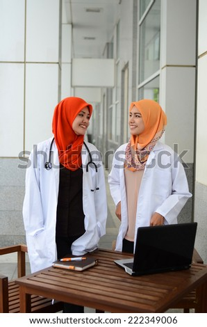 Confident Muslim medical students busy conversation together at hospital - stock photo