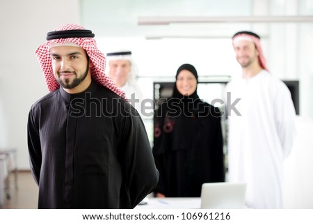 Confident muslim  young business executive with his team in the background - stock photo