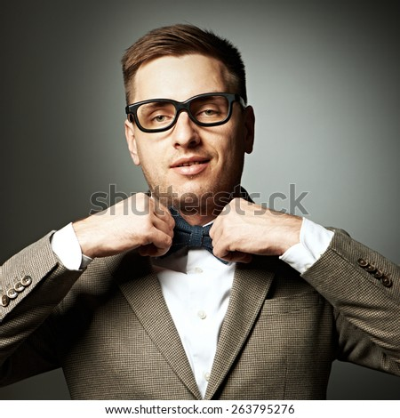 Confident nerd in eyeglasses adjusting his bow-tie against grey background - stock photo
