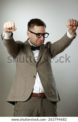 Confident nerd in eyeglasses and bow tie enjoying success against grey background - stock photo