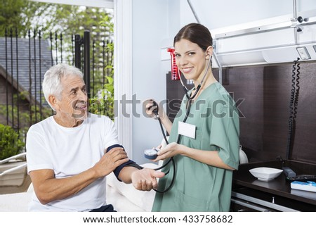 Confident Nurse Examining Blood Pressure Of Senior Man - stock photo