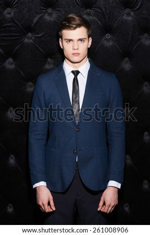 Confident of being the best. Fashionable young man sitting on the chair holding hands on his jacket and looking at camera - stock photo