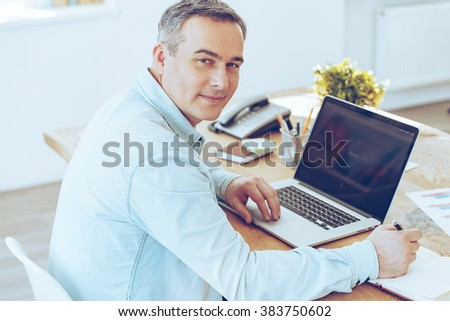 Confident office worker. High angle view of cheerful mature man working on laptop and looking at camera with smile while sitting at his working place - stock photo